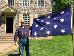 "Pius App in front of General George Washington's headquarters holding the ""Commander-in-Chief"" flag"